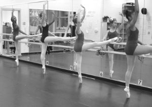 Young Women in ballet class working on their form in front of mirrors.